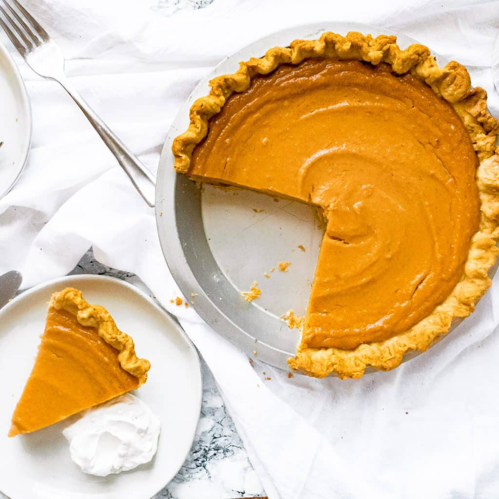 Overhead shot of brown butter sweet potato pie with a slice cut out and whipped cream on the side