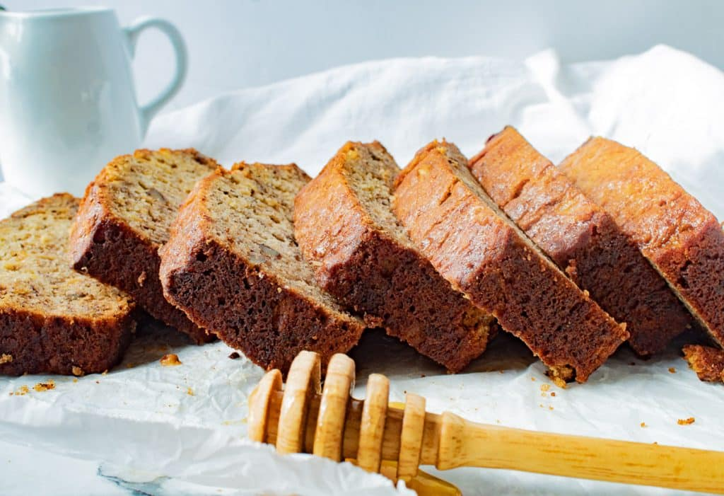 slices of pineapple banana bread with a honey dipper