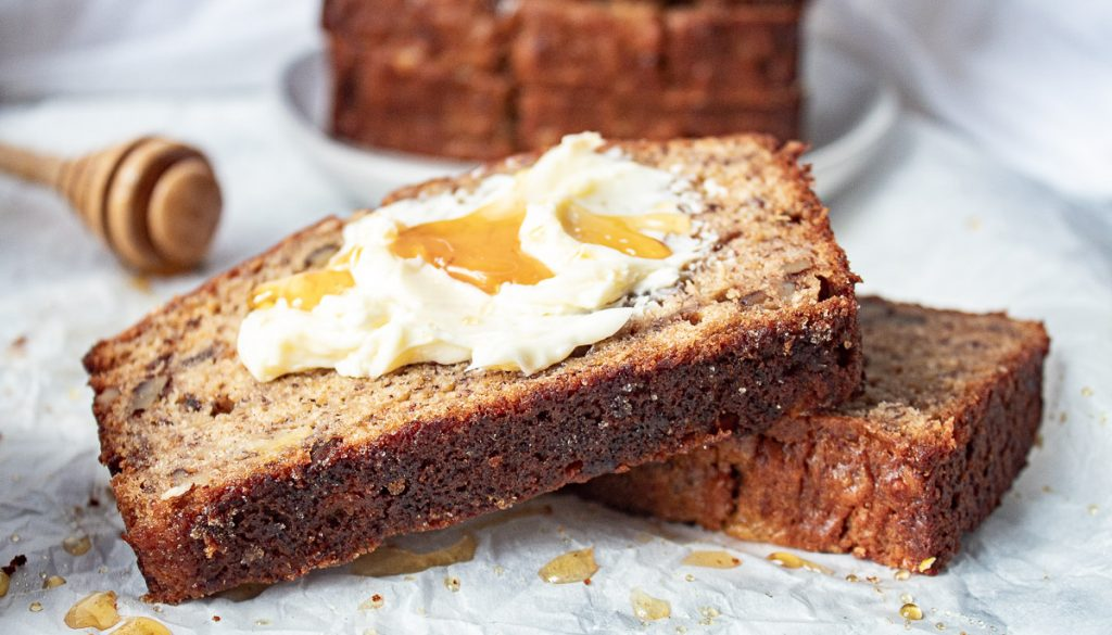 slices of banana bread topped with butter and honey