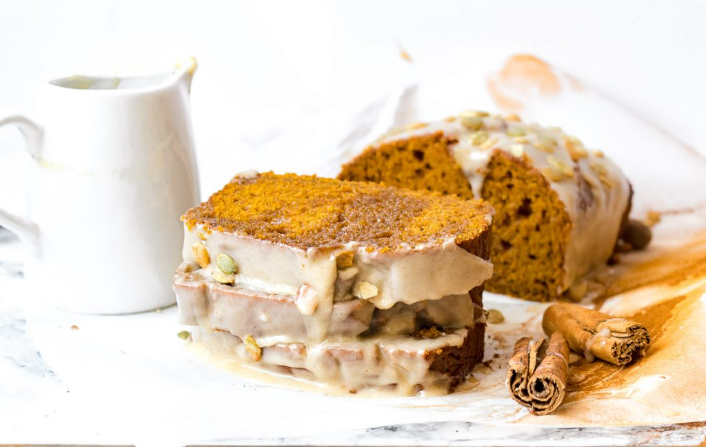 Stack of pumpkin bread next to the loaf, with cinnamon sticks