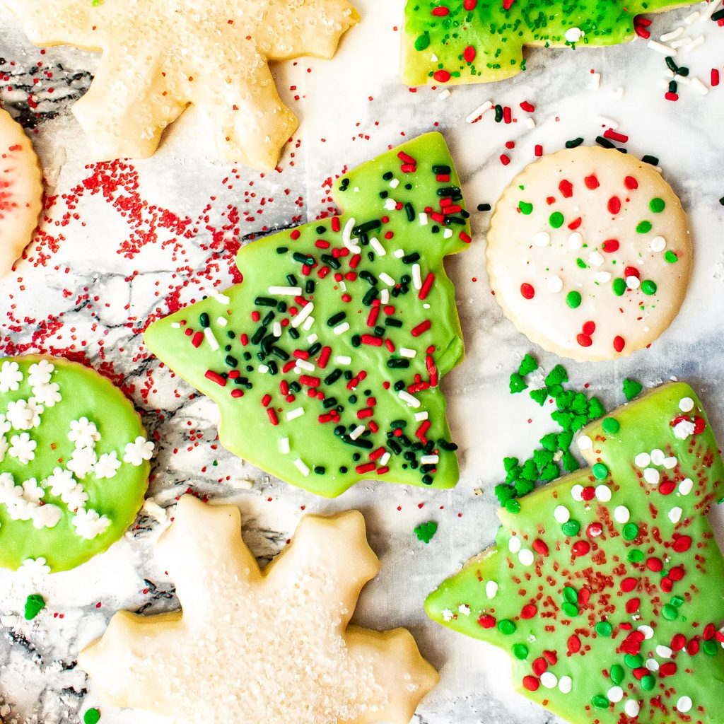 Decorated sugar cookies with sprinkles on parchment paper