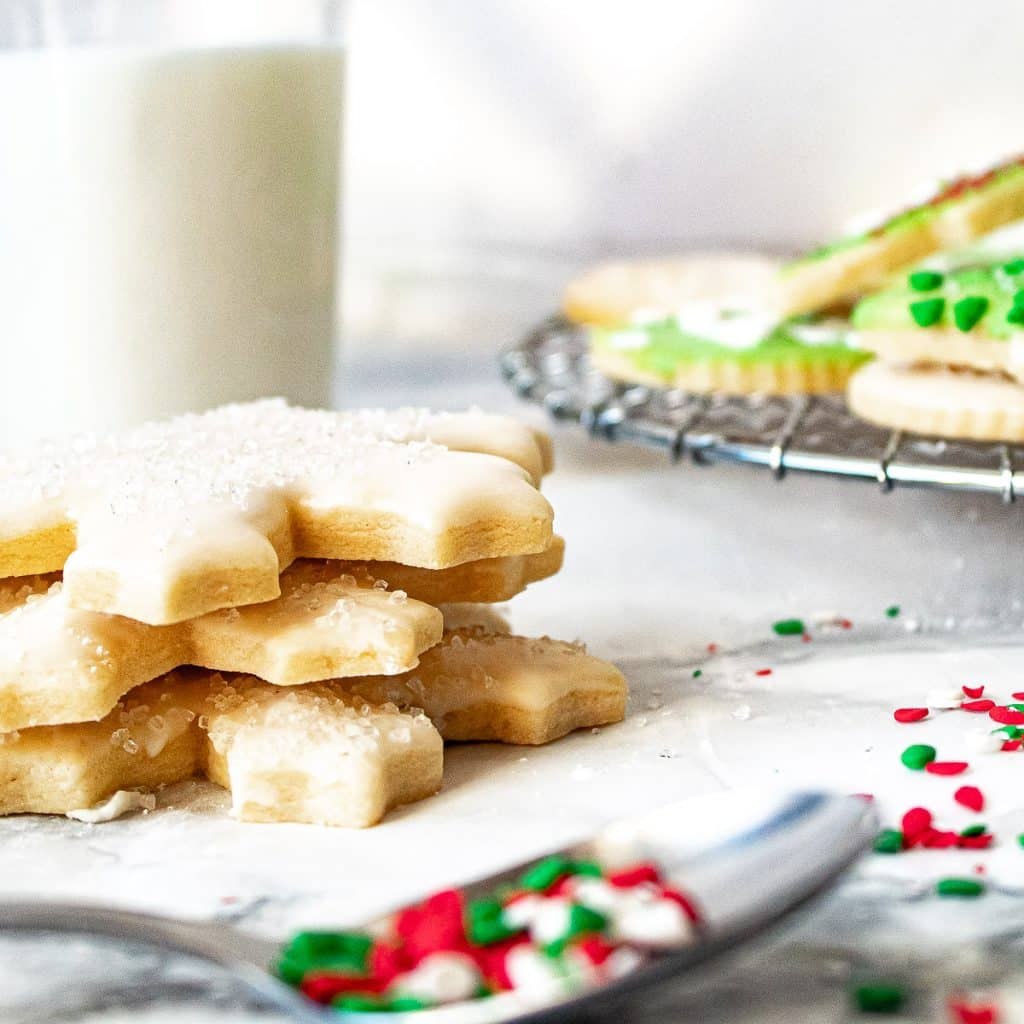 stack of decorated sugar cookies with a glass of milk and more cookies in the background, and a spoon with sprinkles in the foreground