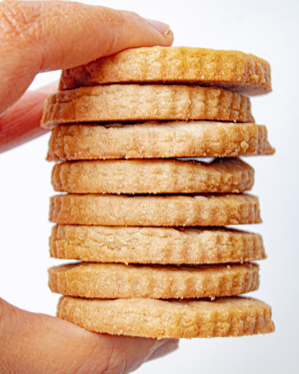 a hand holding a stack of brown sugar shortbread cookies