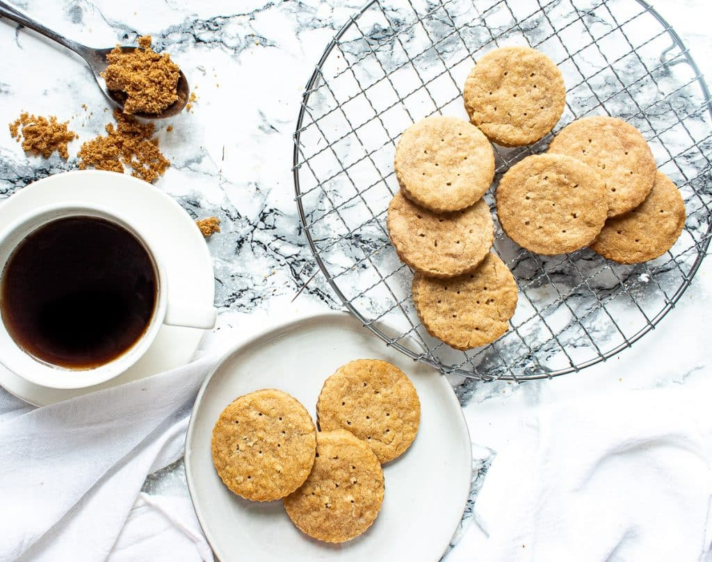 brown sugar shortbread cookies on a wire rack and then some on a plate, with a cup of coffee