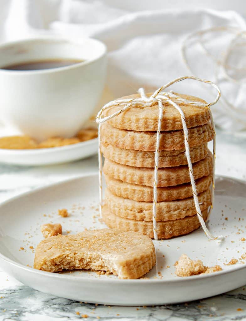 stack of brown sugar shortbread cookies tied with string, with a cup of coffee in the background