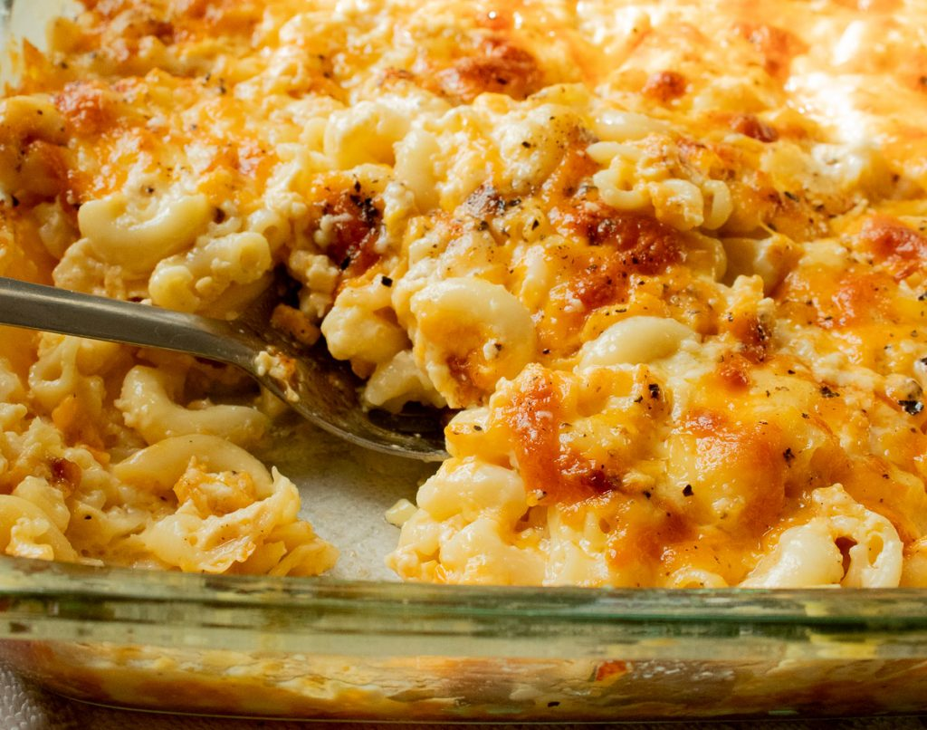 spooning baked macaroni and cheese from the pan