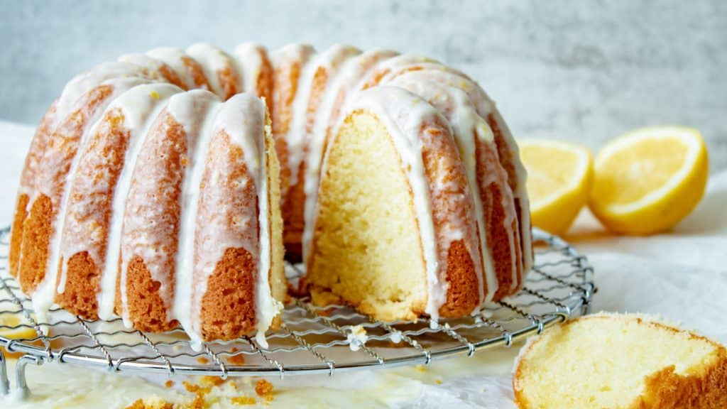 lemon sour cream pound cake on a wire rack with slices cut out