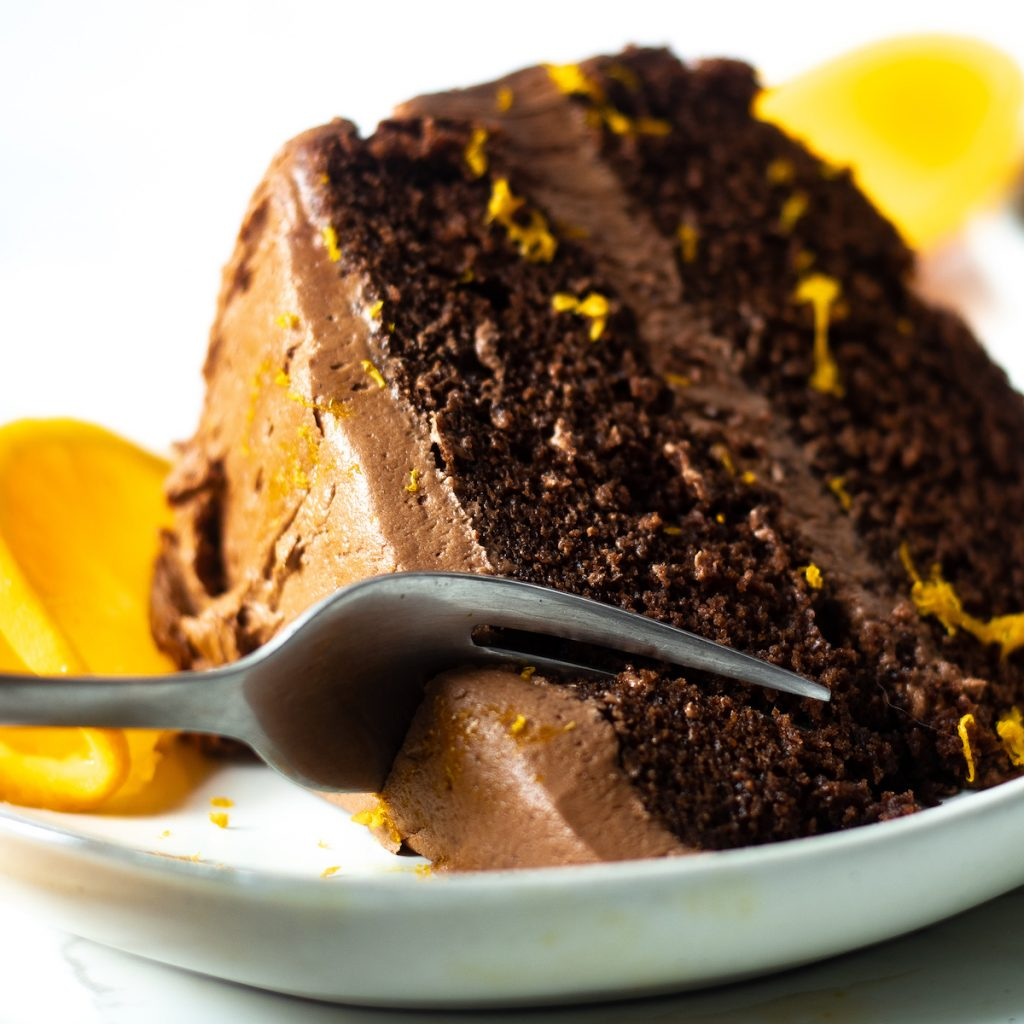 slice of dark chocolate orange cake being cut with a fork, with an orange and orange zest as garnish