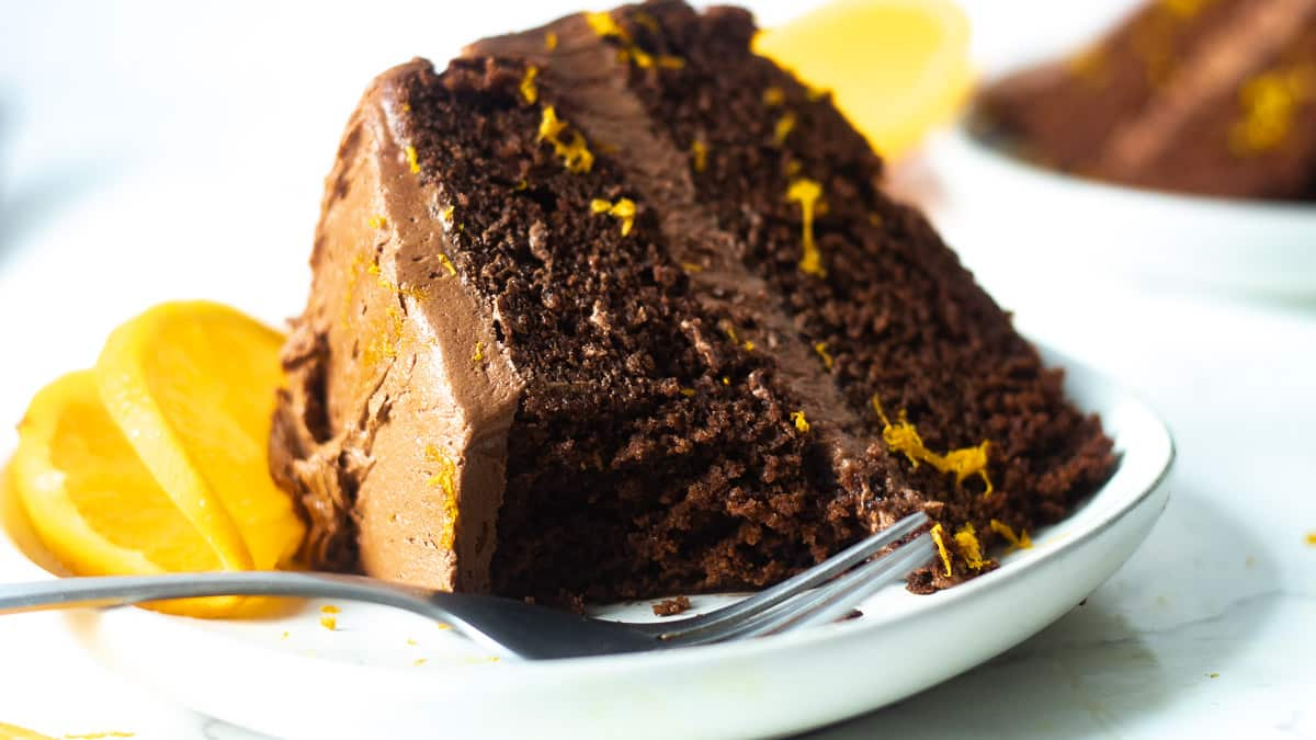 dark chocolate orange cake with a piece cut out of it