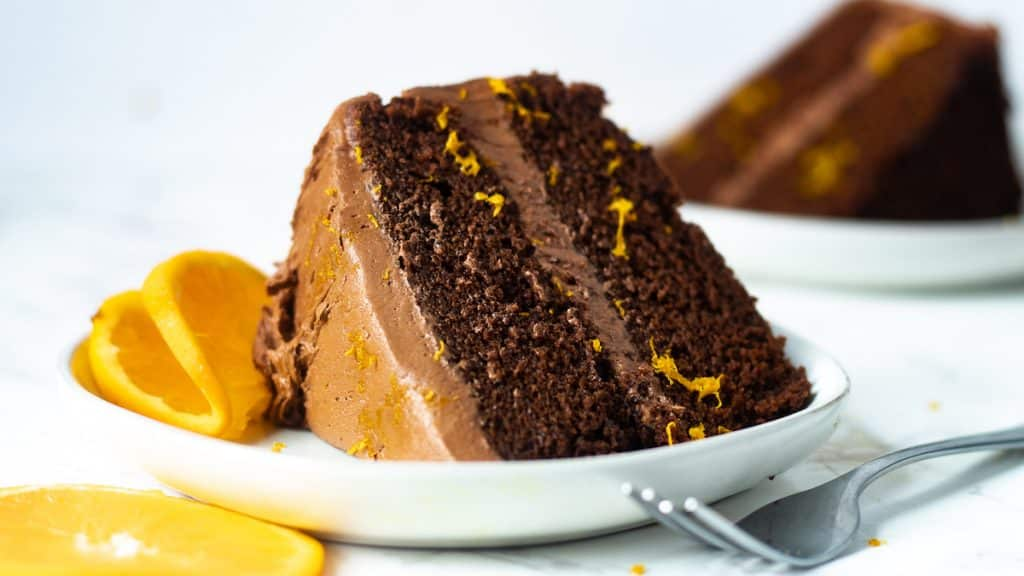 moist chocolate orange cake on a plate with a fork and another slice of cake in the background