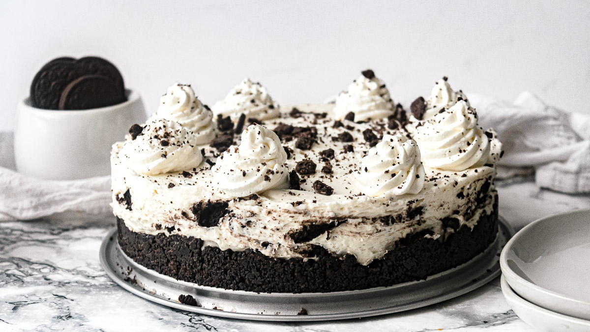 whole no bake Oreo cheesecake with cool whip and Oreos in the background