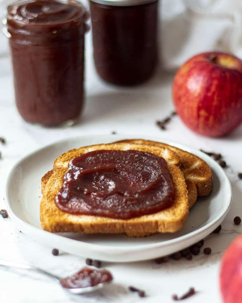 Apple butter spread onto toast with jars of apple butter and an apple nearby