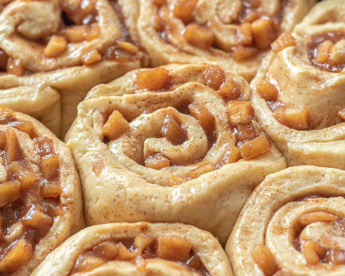 Closeup of cinnamon rolls with apple pie filling before baking