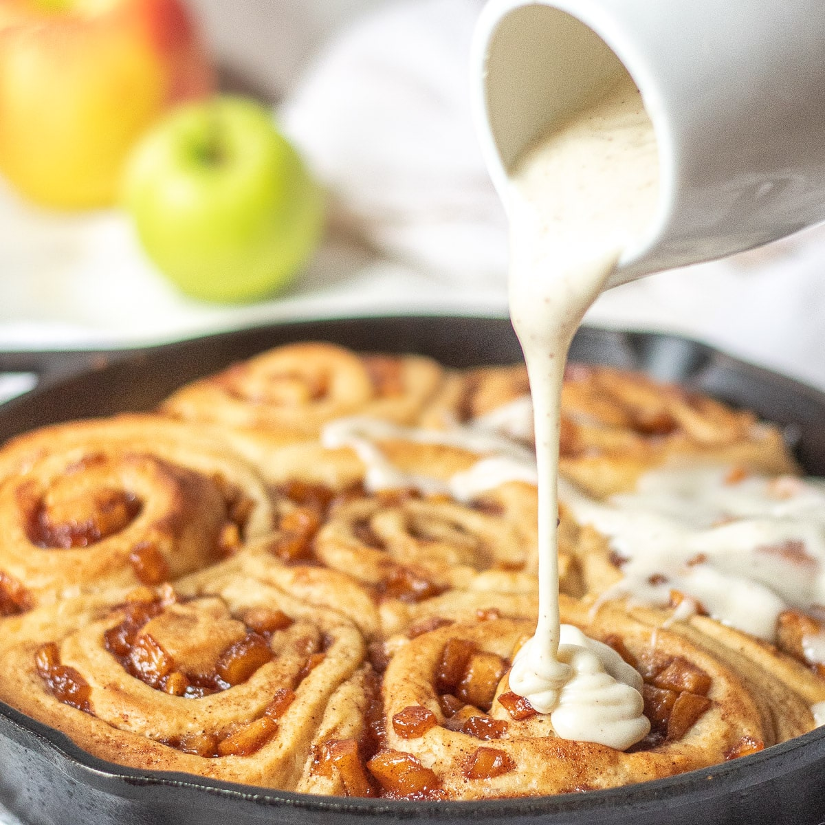 Apple Pie Cinnamon Rolls baked in a cast iron skillet, being drizzled with brown butter cream cheese glaze with apples in the background
