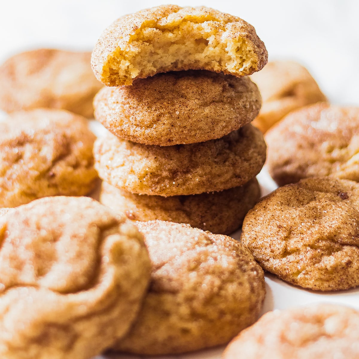 stack of snickerdoodles with more snickerdoodles around